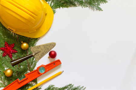 Protective helmet, mason tools  and Christmas decorations on  white background
