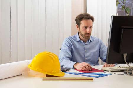 Ingenieur zit achter de computer in zijn kantoor