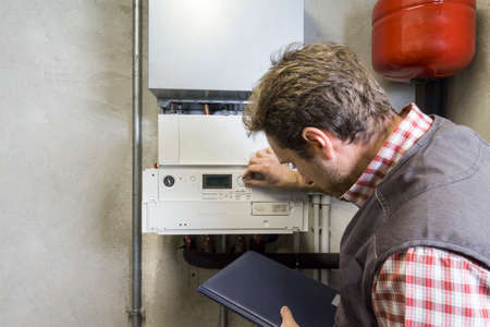 plumber repairing a condensing boiler Archivio Fotografico