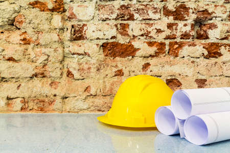 Construction of buildings: safety helmet and  drawings project on brick wall background Stockfoto