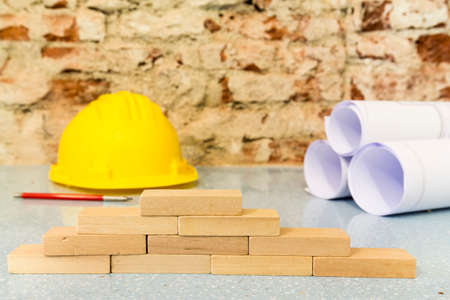 little wooden blocks, safety helmet and  drawings project on brick wall background