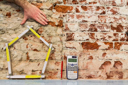 Construction of buildings: house and projects on brick wall background Standard-Bild
