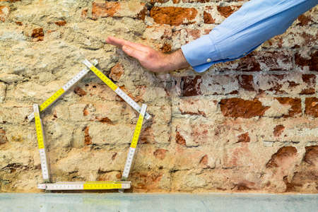 Hand protecting a house, brick wall background Standard-Bild