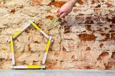 Construction of buildings:  hand building a house on brick wall background Stockfoto