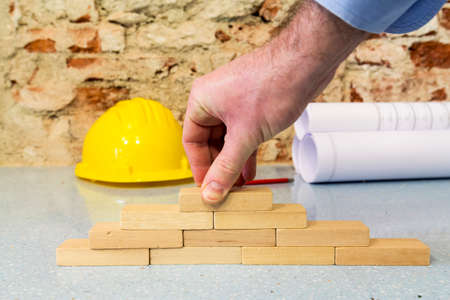 Construction company: hand building a wall in little wooden blocks Stockfoto