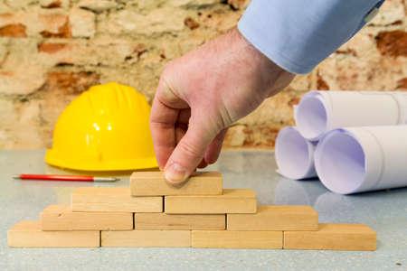 construction company: hand building a wall in little wooden blocks Standard-Bild