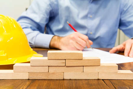 Business man and wall built with small wooden blocks
