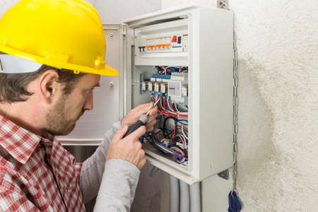 electrician at work on an electrical panel Stockfoto