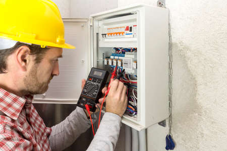 electrician at work measures the electric current Stockfoto