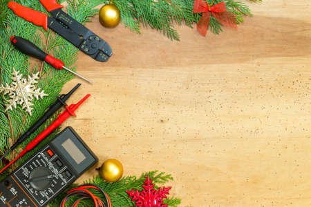 Electrician tools and instruments  and Christmas decorations on wooden background Stok Fotoğraf