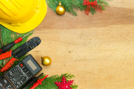 Electrician tools and instruments  and Christmas decorations on wooden background Stockfoto
