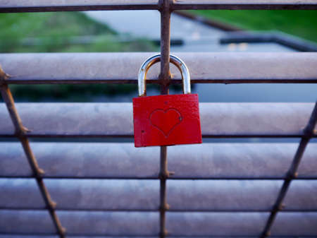 love declaration: Red love lock on a railing with an engraved heart