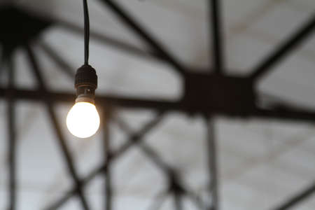 girders: Bare industrial light bulb with roofing girders low key