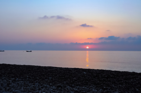 Pastel sunrise on Cirali Beach: Pastel hued sunrise with boats bobbing in ethereal flat waveless water seen from pebble beach in Cirali, Turkey.