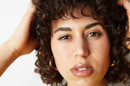 Close-up portrait of young woman with curly hair posing on the white wall. With positive emotions. Space for your text. Stock Photo