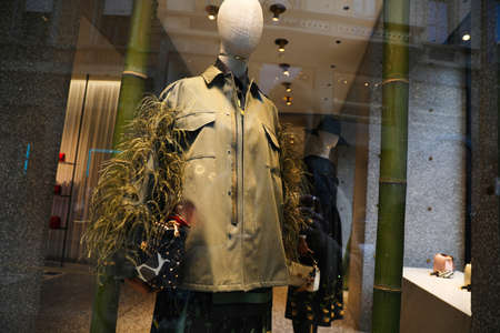 Store window with mannequin wearing fashion clothing.