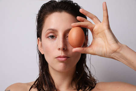 Young woman holding natural egg. Isolated.