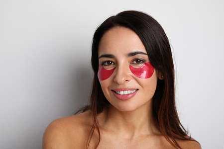 Young woman looking at camera take care of her skin with under eye patches.