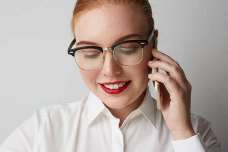 Close-up of stylish young woman wearing casual clothes and listening a voice message from smartphone. Stock fotó