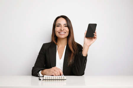 Office secretary young lady posing on the white wall and showing her smartphone. Co-working. Foto de archivo