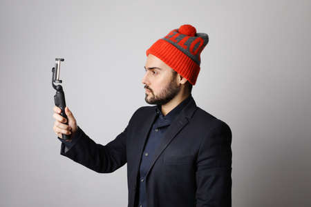 Portrait of young bearded man using selfie-stick and filming himself.