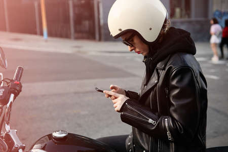 Close-up portrait of biker girl checking her smartphone and wearing white helmet.