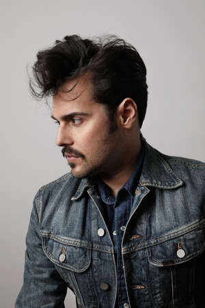 Profile shot of serious stylish hipster looks aside with confident expression, wears denim jacket, isolated over white background.