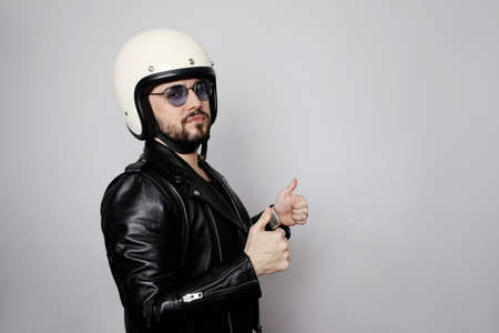 Close-up portrait of young happy biker man with white cafe-racer helmet. White background.