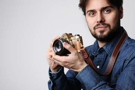 Young bearded man with taking photos using vintage camera, isolated over white background.