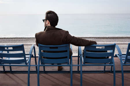Outdoor shot of a young bearded man sitting on the bench in the bay enjoying a nice view.