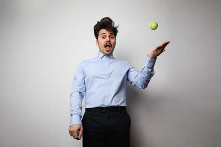 Image of serious young man holding tennis ball while working in office.