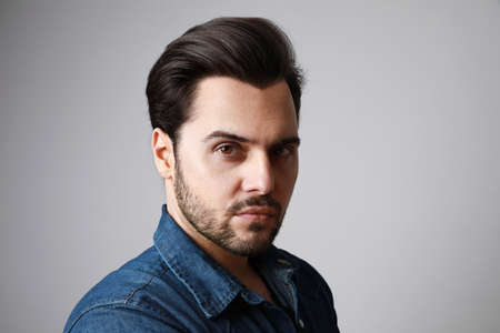 Portrait of 30-year-old man standing over grey background in denim shirt. Close up. Copy-space. Studio shot. Imagens