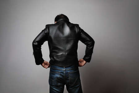 Portrait of man wearing leather jacket stands back in the studio.