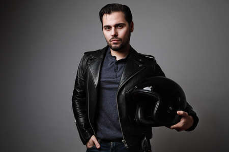 Bearded man wearing a black leather jacket holds helmet in his hands. Lifestyle, travel. Copy space.