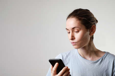Lifestyle headshot woman on phone texting text message on smartphone app indoor. Caucasian female model in her 20s.