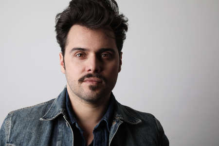 Headshot of serious stylish man looks straight with confident expression, wears denim jacket, isolated. Banque d'images