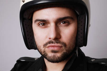 Handsome bearded man over white background with serious face wearing white helmet. Stock Photo