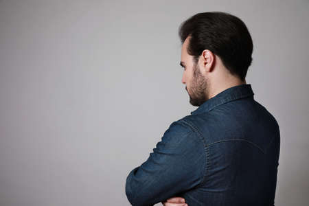Silhouette of a European bearded man from the back in a casual shirt look to the side. Space for text.