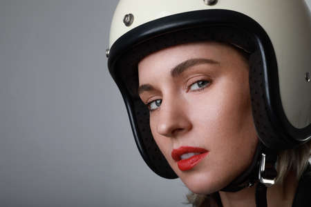 Close-up portrait of biker young woman, wearing white helmet, with red lips. Blue background. Space for your text.