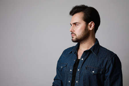 Side view of bearded man in the denim outfit which mixed with bright white t-shirt posing over white wall.