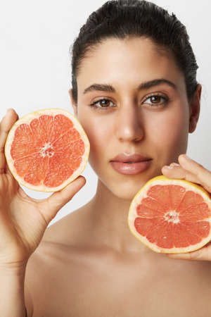 Vertical portrait of young beautiful woman with two oranges posing over white background. Healthy and clean eating. Stock Photo