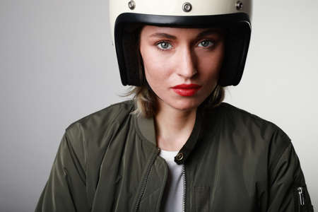 Close-up portrait of happy biker young woman, wearing retro helmet, with red lips. Space for your text.
