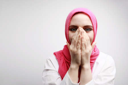 Indoor head shot of optimistic Muslim woman with surprising face expression closing her mouth with two hands. 免版税图像