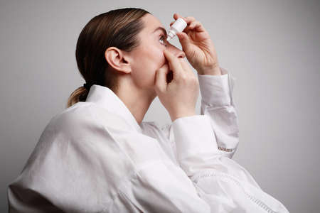 Woman with injured eye inserting eye-drop. Health care and eyesight concept. Conjuctivitis. Woman with injured eye