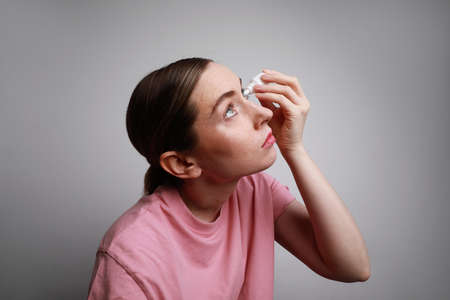 Woman has eye allergy and inserting eye-drop. Health care and eyesight concept. Conjuctivitis. Woman with injured eye
