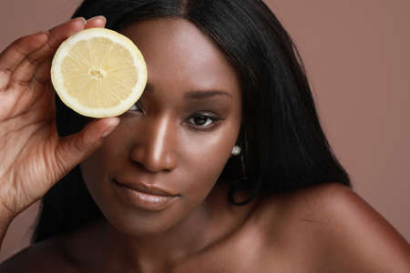 Close-up photo of beautiful dark skin model lady holding slice of citrus vitamin c fruit isolated brown background. Banco de Imagens