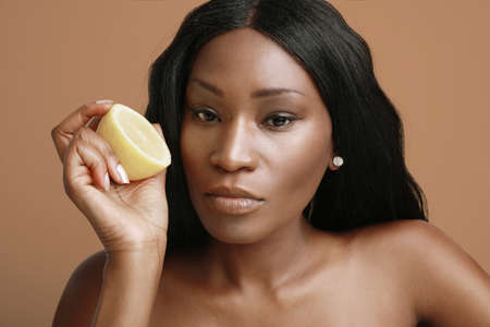 Close-up of young and beautiful dark skin model lady holding slice of citrus vitamin-c fruit isolated brown background.