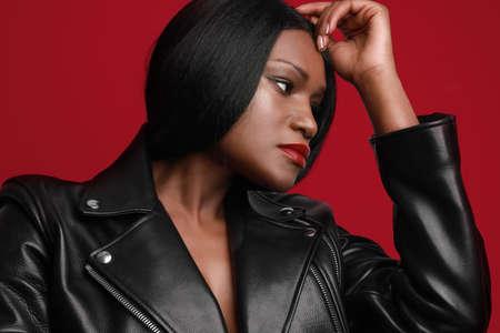 Headshot of young black female model looking aside, wearing biker jacket posing over red wall. Studio Shot.