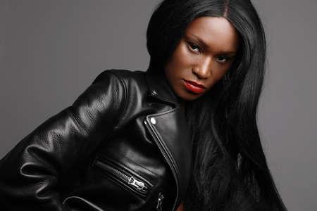 Headshot of young black female model, wearing biker jacket posing over grey wall. Studio Shot. 版權商用圖片
