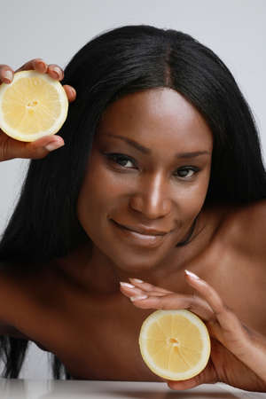 Vertical close-up photo of beautiful dark skin woman holding slices of citrus vitamin c fruit isolated white background.